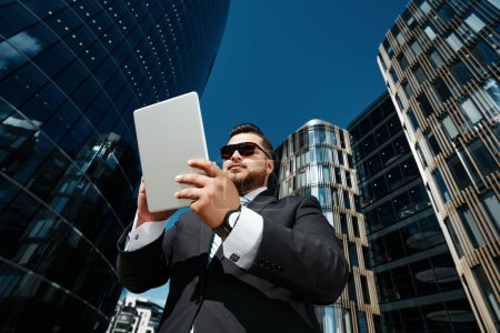 Bottom view portrait of successful business man using touch pad