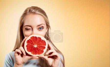 Young blonde woman with grapefruit in her hands studio portrait