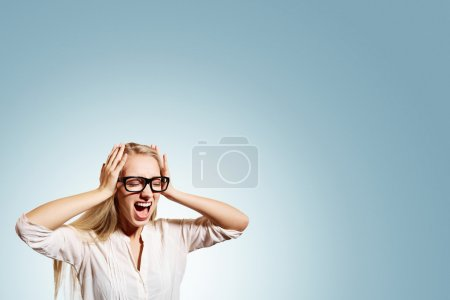 Photo for Portrait upset stressed young blonde business woman squeezing her head, going nuts, screaming, losing her mind, looking up isolated blue wall background. Negative emotion feeling reaction - Royalty Free Image