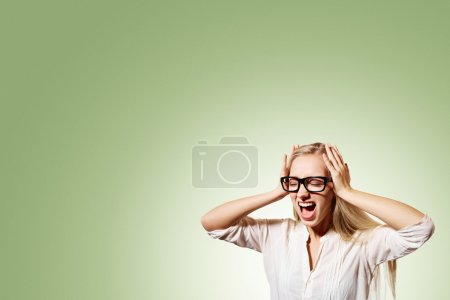 Photo for Portrait upset stressed young blonde business woman squeezing her head, going nuts, screaming, losing her mind, looking up isolated pistachio wall background. Negative emotion feeling reaction - Royalty Free Image