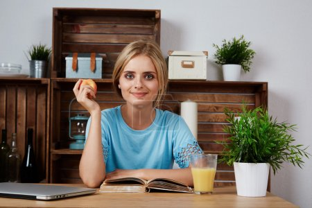 Young blonde woman studying for university at home, sitting at desk with books and laptop computer, smiling at camera