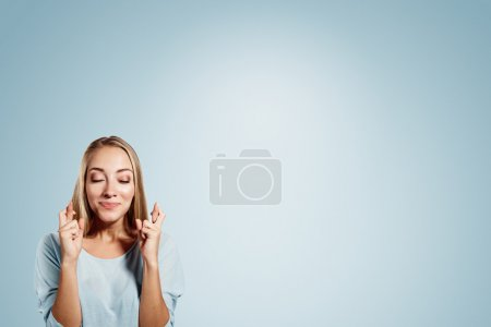 Close-up portrait of a beautiful woman closing her eyes, crossing her fingers hoping for the best,isolated on blue background