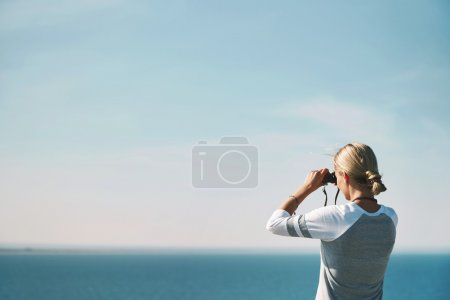 Photo for Woman tourist looking through binoculars at distant sea, enjoying landscape - Royalty Free Image