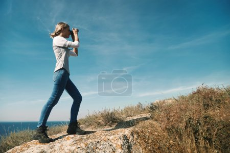 Girl with binoculars at the mountains in the rays of the evening