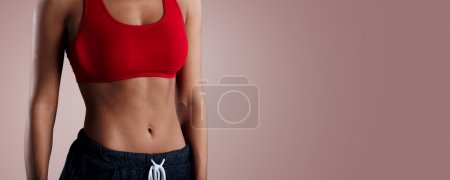 Beautiful mixed race sporty woman with slim stomach isolated over background.
