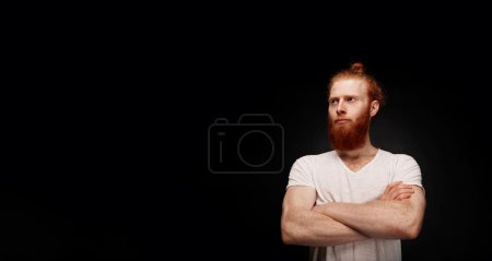 Optimistic portrait of handsome young bearded man standing against black wall with copy space.