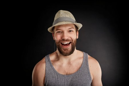 Happy smiling handsome hipster man posing. Bearded man in t-shirt looking at the camera isolated on black background.