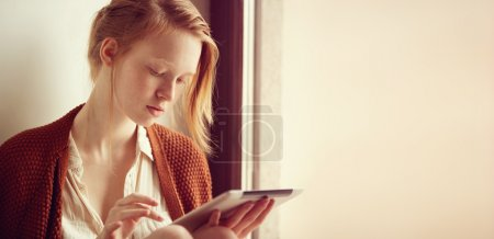 Relaxed young mixed race woman in sofa smiling content, happy and reading on tablet pc at home. Lifestyle image of beautiful ?aucasian redhead and freckled girl relaxing. Free space for your text.