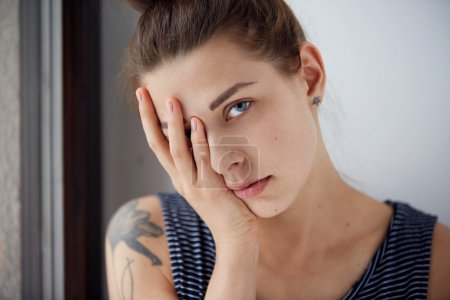 Frustrated stressed young woman. Headshot unhappy overwhelmed girl having headache bad day keeps hands on face out isolated on wall background. Negative emotion face expression feelings perception.