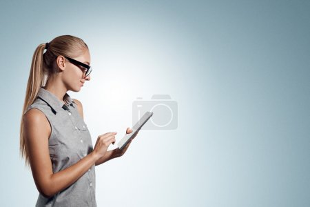 Tablet computer. Business woman using digital tablet computer PC happy isolated on white background. Beautiful woman in business shirt with finger on touch screen display.