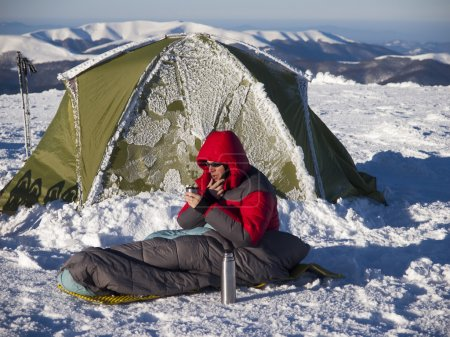 Photo for A man sits in a sleeping bag near the tent and drinking tea from a thermos on the background of the winter mountains. - Royalty Free Image