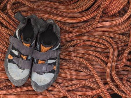 Photo pour Chaussures pour l'alpinisme et l'escalade est sur la corde orange . - image libre de droit