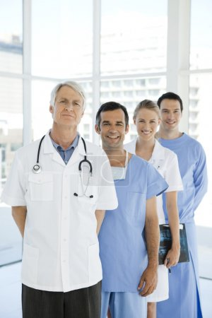 Photo for Medical staff standing in a row behing senior leader in a hospital lobby - Royalty Free Image