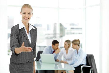 Photo pour Femme d'affaires attrayant debout au premier plan avec le personnel des jeunes gens d'affaires lors d'une réunion sur le fond. Mise au point sélective sur manager féminin. - image libre de droit