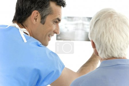 Surgeon showing x-ray image to senior patient