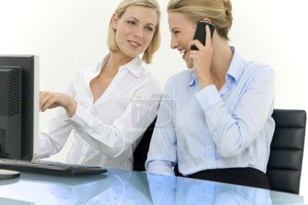 Photo pour Deux jolies femmes travaillant ensemble sur lieu de travail. Ils regardent de l'autre. - image libre de droit