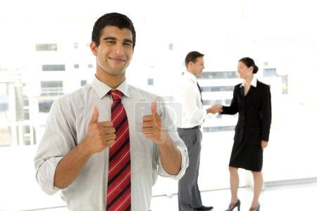 Photo pour Portrait d'un jeune homme d'affaires indien debout dans un hall d'accueil avec les pouces vers le haut, avec deux partenaires commerciaux se serrant la main dans le fond. Mise au point sélective sur lui. - image libre de droit