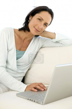 Middle aged woman using pc at home