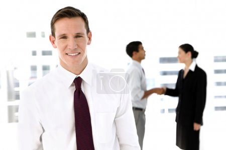 Photo pour Portrait d'un jeune consultant mâle avec ses partenaires, se serrant la main dans le fond. - image libre de droit