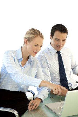 Photo pour Couple de gestionnaires travaillant ensemble sur ordinateur portable. Femme pointant sur l'écran de l'ordinateur. Studio coup isolé sur blanc. - image libre de droit