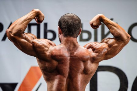 Photo for Athlete bodybuilder in competition. view from back - Royalty Free Image