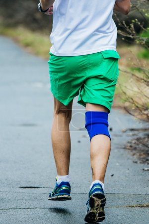 young athlete man running down road