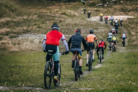 group of cyclists mountainbikers riding on a mountain