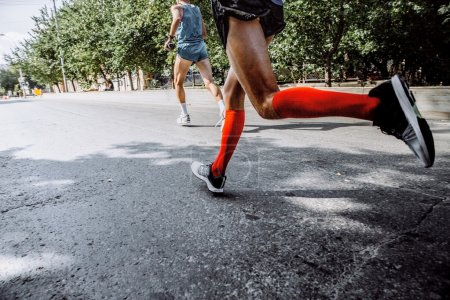 Photo for Male athlete running in compression socks on city street marathon - Royalty Free Image