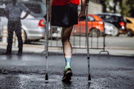 Photo pour Athlète masculin ayant un handicap sans une jambe sur des béquilles courir marathon - image libre de droit