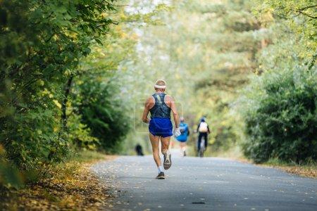 back oldest male runner marathon running in autumn Park