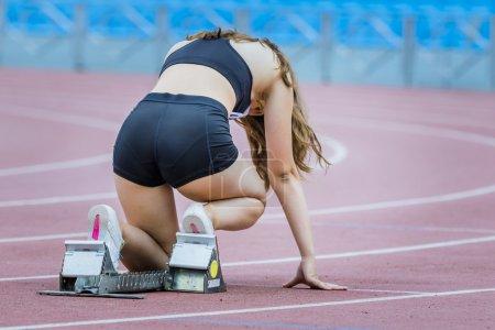 Photo pour Athlète fille en position de départ sur une piste sportive - image libre de droit