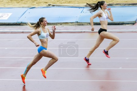 Girl athletes run 400 meters in the rain