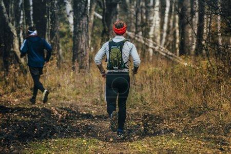 two men running through woods