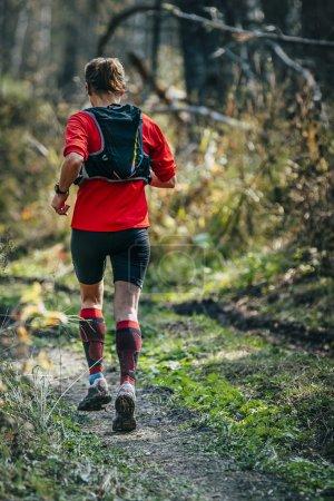 woman runner running through the woods