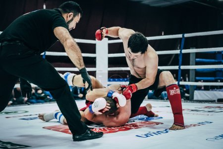 MMA fighter strikes hand on head of an opponent lying on floor  ring