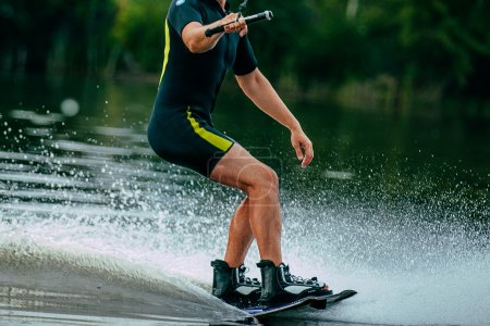 man rides a wakeboard on lake