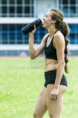 Beautiful girl athlete drinking water