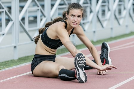 sport girl doing stretching exercise in stadium