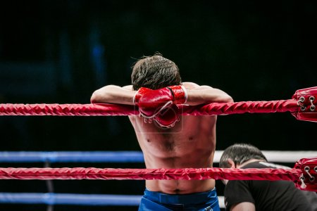 mixed martial arts fighter (MMA) stands in corner ring