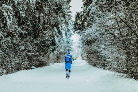 man in sportswear running through alley in winter forest