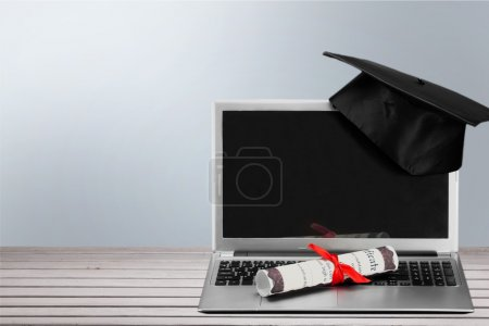 Photo for Laptop and diploma scroll on background - Royalty Free Image