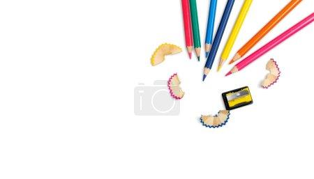 Foto de Algunos lápices de colores de diferentes colores y un lápiz virutas de lápiz y sacapuntas sobre un fondo blanco - Imagen libre de derechos