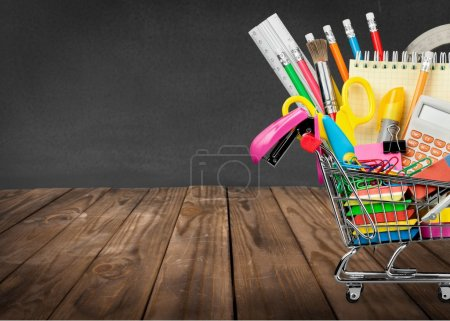 Photo for Assortment  of School supplies in shopping cart on  background - Royalty Free Image