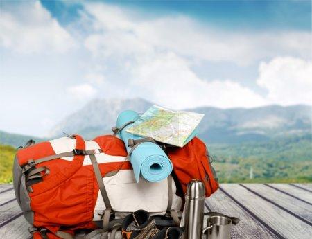 Foto de Mochila con mapa y termo aislado sobre fondo. Temas de viajes y Turismo. - Imagen libre de derechos
