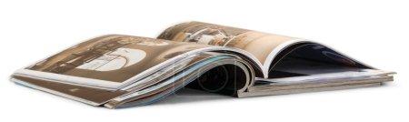 Photo pour Pile de magazines sur papier glacé ouvertes isolé sur fond blanc - image libre de droit