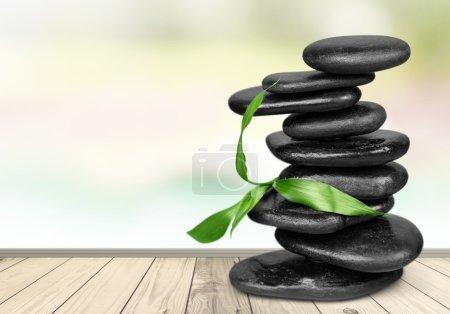 Photo pour Pierres de basalte zen et feuilles sur fond - image libre de droit