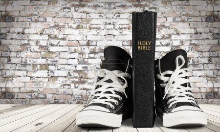 Photo for Pair of new black  sneakers and Holly Bible isolated on background. - Royalty Free Image