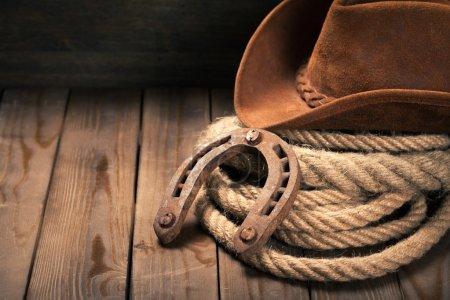Photo pour Vieux fer à cheval, lasso lasso et chapeau de cowboy sur fond - image libre de droit
