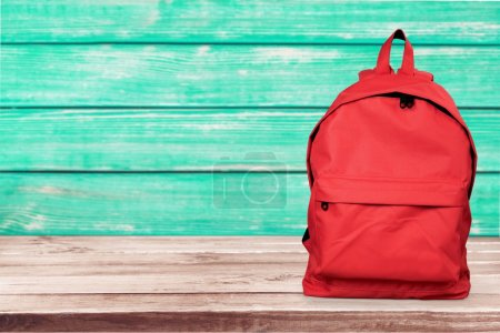 Red backpack on wooden surface