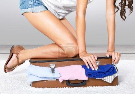 Photo pour Jeune femme valise d'emballage, en essayant de le fermer - image libre de droit